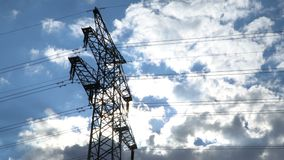 Electricity transmission pylon silhouetted against blue sky at dusk.  stock video