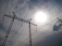 Electricity transmission pylon silhouetted against blue sky at dusk royalty free stock photo
