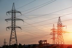 Electricity transmission pylon silhouetted against blue sky at dusk. royalty free stock photography