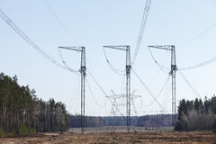 Electricity transmission pylon silhouetted against blue sky. In the woods, at sunset stock image