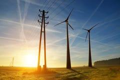Electricity transmission pylon and wind turbines Stock Photos