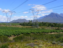 Electricity valley. Electricity pylons stand tall in a valley with the N1 national highway and mountain range in the distance near Rawsonville- South Africa Stock Photos