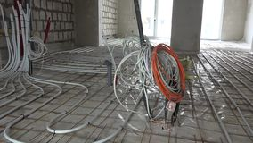 Electricity wire installation and floor heating system tubes before concrete lay stock footage