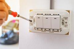 Electrictian que parafusa o interruptor de alimentação na casa Fotografia de Stock Royalty Free