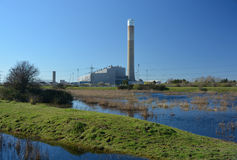 Electricty Power station. An electric generating power plant surrounded by fields and water Stock Image