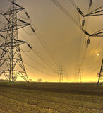 Electricty Pylons. In a farmers field, early morning royalty free stock photos