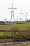 Electricty pylons in the UK countryside. Electricity pylons criss crossing the agricultural landscape of north Devon UK Royalty Free Stock Photo