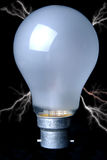Electrified Light Bulb. Light bulb against black background with lightning bolts Royalty Free Stock Photos