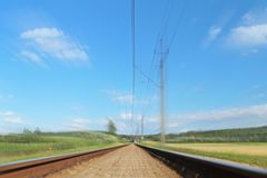 An electrified railway track among green meadows and wheat fields. Railway Transportation Infrastructure. Safety of the transport. System. Ecology of royalty free stock image