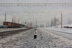 Electrified railway tracks  -and railway station with traffic sign in winter Stock Photos