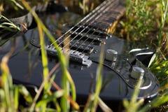 Electro gitarr som ligger i gräs Arkivbild
