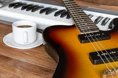 Electro guitar, piano and cap of coffee Stock Photos