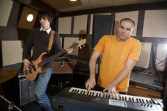 Electro guitar player and keyboarder in studio. Electro guitar player and keyboarder working in studio Royalty Free Stock Image