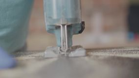 Electro jigsaw cutting a chipboard. Furniture manufacture. Concept of hand manufacturing. Craftman works in a workshop.