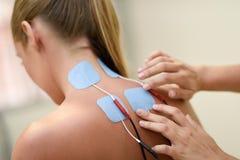 Electro stimulans i sjukgymnastik till en ung kvinna royaltyfria bilder