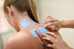 Electro stimulation in physical therapy to a young woman. Medical check at the shoulder in a physiotherapy center Royalty Free Stock Images
