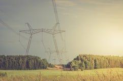 Electro torres de alto voltaje/electro torres de alto voltaje contra en una puesta del sol del fondo fotografía de archivo libre de regalías