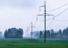 Electro transmission line. Large power lines with air ducts visible through the forest during fog; green cereal fields are in the foreground; electro royalty free stock photo