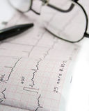 Electrocardiogram. On the table with glasses and a pen Royalty Free Stock Photography