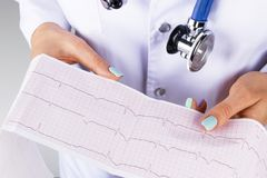 Electrocardiogram, ecg in hand of a female doctor. Medical health care. Clinic cardiology heart rhythm and pulse test closeup. Cardiogram printout stock image