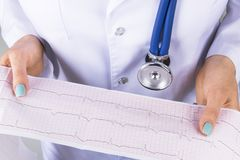 Electrocardiogram, ecg in hand of a female doctor. Medical health care. Clinic cardiology heart rhythm and pulse test closeup. Cardiogram printout royalty free stock image