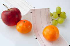 Electrocardiogram with fruit. Test results of an electrocardiogram and fruit like an apple, two tangerines and grapes Royalty Free Stock Photos
