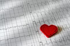 Electrocardiogram on paper.  Red heart made of fabric stock photo
