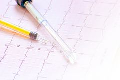 Electrocardiogram with syringe and bottle. ECG examination completed with specific chemical blood analysis Stock Images