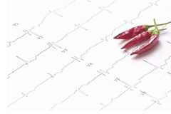 Electrocardiogram with three dehydrated chillies grouped. ECG evaluation and red chili suggesting the effect of spicy food Royalty Free Stock Images