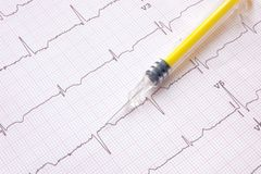 Electrocardiogram with yellow colored syringe. Electrocardiogram with colored syringe suggesting a heart issue treatment Royalty Free Stock Image