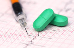 Electrocardiograph with pills and syringe Stock Photo