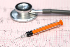 Electrocardiograph with stethoscope and syringe Stock Image