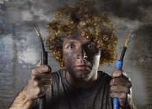 Electrocuted man with cable smoking after domestic accident with dirty burnt face shock electrocuted expression Stock Photo