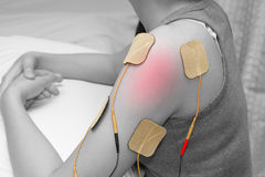 Electrodes of tens device on shoulder, tens therapy royalty free stock photo