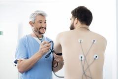 Electrodos del doctor Examining Patient With atados encendido detrás foto de archivo libre de regalías