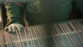 Electrodos para soldar con autógena en el transportador El trabajador en el transportador endereza los electrodos almacen de video