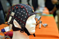 The electroencephalogram EEG head cap with flat metal discs electrodes attached to a white plastic model's head Stock Photography