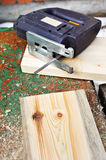 Electrofret saw and wooden board Stock Photography