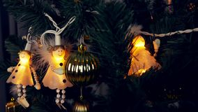 Electrogarlands of white angels are hanging on a Christmas tree. Beautiful cute white angels shine in the dark. Christmas Eve and New Year`s Eve. Low key stock footage