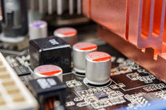 Electrolytic capacitors installed on the motherboard closeup stock image