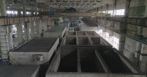 A beam crane transports barrels. A large crane in production. Beam crane. Industrial interior at the factory