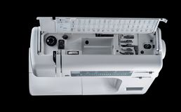 Electromechanical modern sewing machine white plastic top view on an additional technical department on a black background,. Isolate royalty free stock photos