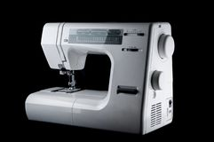 Electromechanical modern white plastic sewing machine on a black background, isolate.  royalty free stock photos