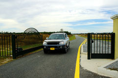 Electronic Access Gate. SUV passing througha restricted community's main acceess gate Royalty Free Stock Image