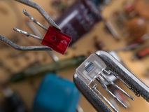 Electronic assembly. Optocoupler and LED in pincers electronic assembly macro Stock Photos