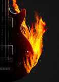 Electronic bass guitar on fire. Electronic bass guitar enveloped flames on a black background Stock Photos