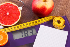 Electronic bathroom scale, centimeter and fresh fruits with stethoscope, slimming and healthy lifestyles Royalty Free Stock Photo