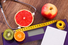Electronic bathroom scale, centimeter and fresh fruits with stethoscope, slimming and healthy lifestyles Stock Photo