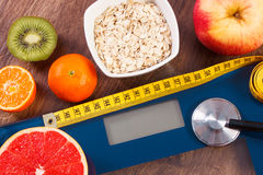 Electronic bathroom scale, centimeter and stethoscope, healthy food, slimming and healthy lifestyles concept Royalty Free Stock Photography