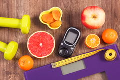 Electronic bathroom scale, glucometer, centimeter, healthy food and dumbbells for fitness, healthy lifestyles, diabetes and slimmi Royalty Free Stock Photo